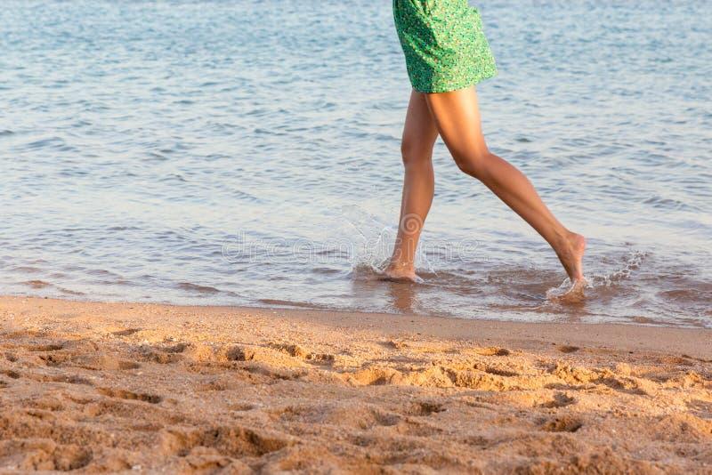 Beautiful girl legs running on the beach. pretty girl walking on water stock photography