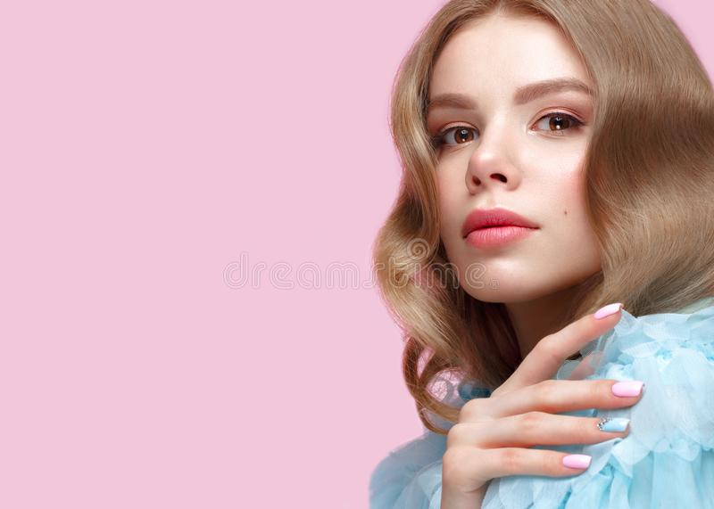 Beautiful girl with light make-up and gentle manicure in blue clothes. Beauty face. Design nails. Photo taken in studio on pink background royalty free stock images