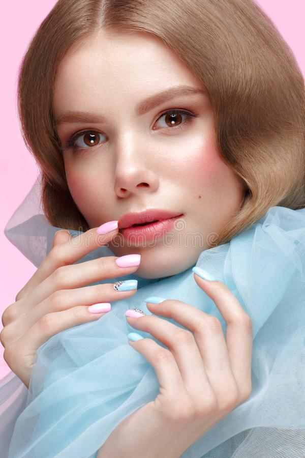 Beautiful girl with light make-up and gentle manicure in blue clothes. Beauty face. Design nails. Photo taken in studio on pink background stock image