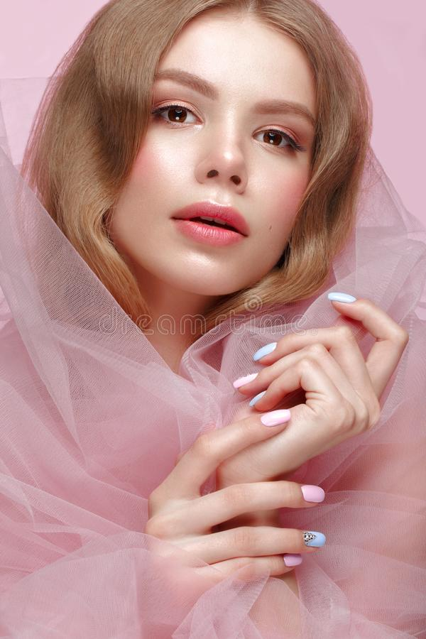 Beautiful girl with light make-up and gentle manicure in pink clothes. Beauty face. Design nails. Photo taken in studio on pink background royalty free stock photography