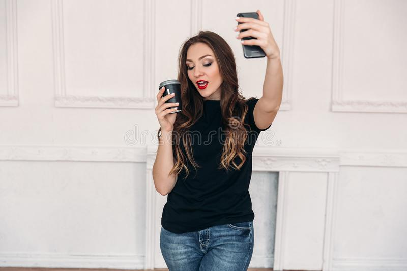 Beautiful girl in a light studio drinks coffee and makes selfie on the phone. A wonderful model with curly hair and red. Lips with a mug of drink in hand. A stock photography