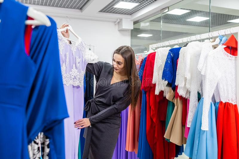 Beautiful girl with lilac dress near mirror on room background. Happy young woman choosing clothes in mall or clothing royalty free stock image