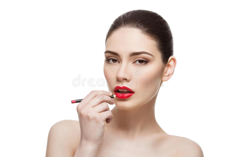 Beautiful girl with lip pencil. Beautiful young woman applying red lip pencil. Isolated over white background. Beauty shot royalty free stock photography