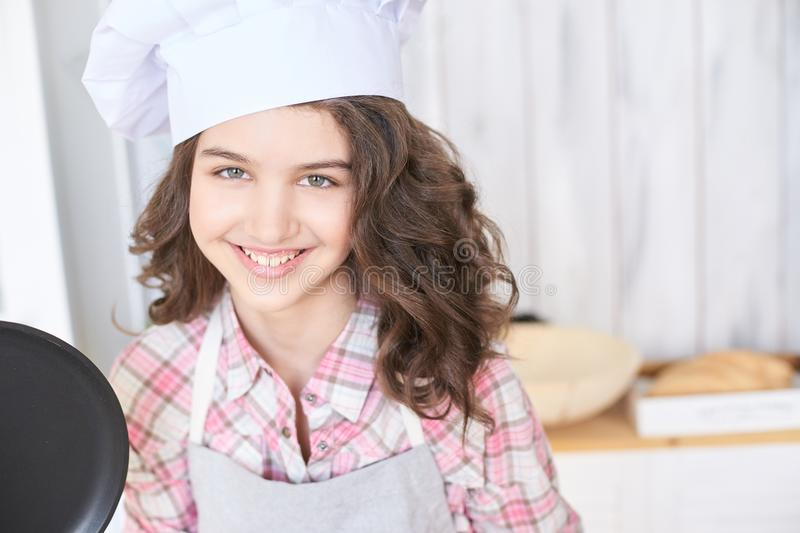 Beautiful girl. Little cook. White cap. Brown curly hair royalty free stock photo