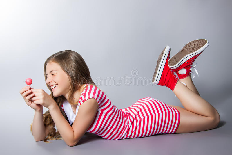 Beautiful girl with a lollipop in her hand is posing on a gray background. girl in a dress in red with white stripes. fashion royalty free stock images