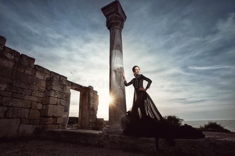 A beautiful girl in a long black dress poses at sunset amid the sea, antique columns and ruins. royalty free stock image