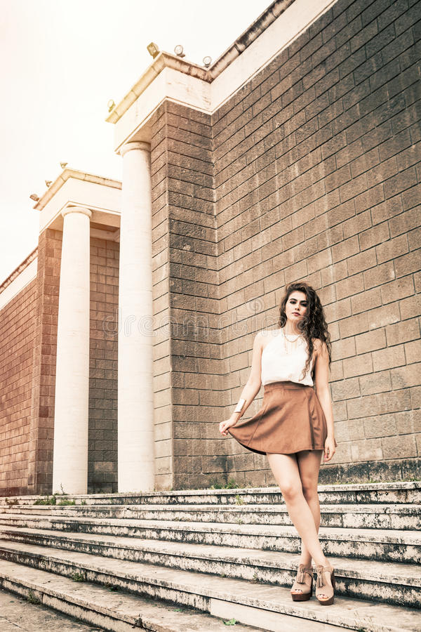 Beautiful girl with long curly hair and skirt. Outdoor. stock photo
