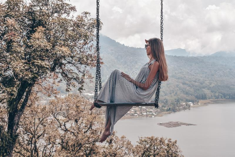 Beautiful girl with long dark hair in elegant grey dress posing stock image