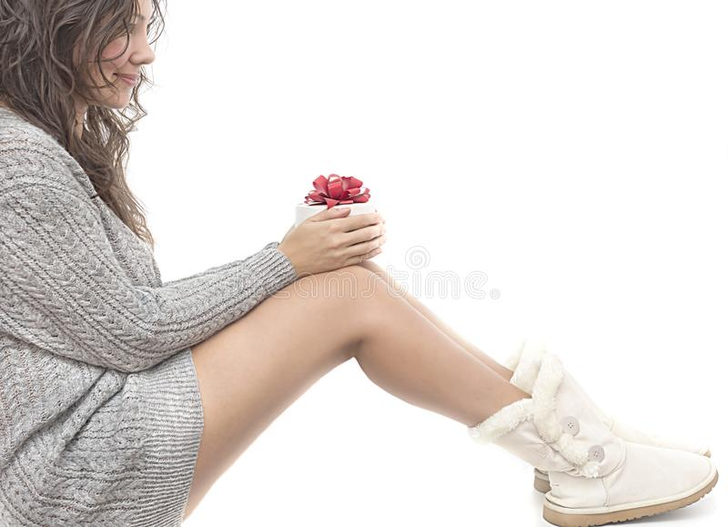 Beautiful girl with long dark hair holding giftbox with Christmas present. Woman in gray winter sweater and white boots. royalty free stock images