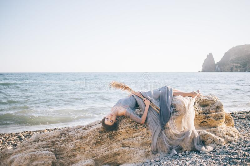 Beautiful girl in a long dress with a veil, lace, tulle, lies on a large white stone on the beach, royalty free stock images