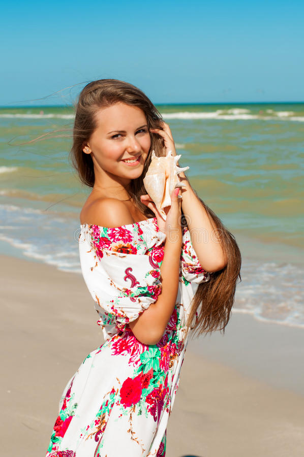 Beautiful girl with long hair on the beach with se. Ashell in hands stock photo