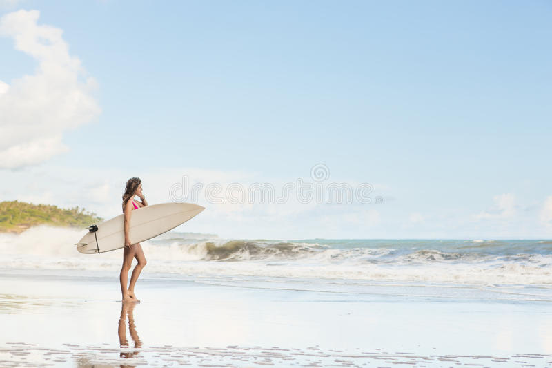 Beautiful girl with long hair on the beach with surfboard royalty free stock image