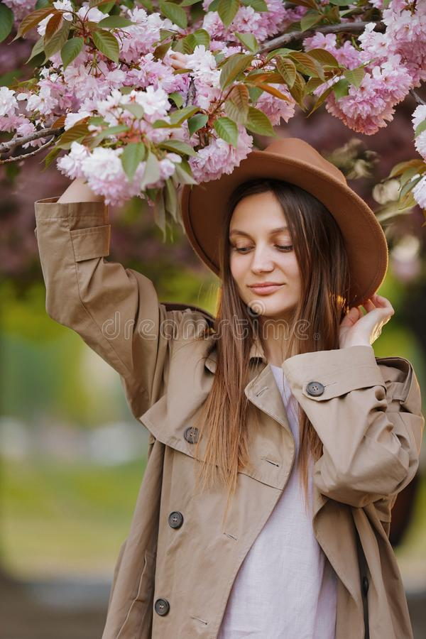 Beautiful girl with long hair holding sakura branch among pink cherry blossoms in spring. Model wearing stylish accessories and cl royalty free stock image
