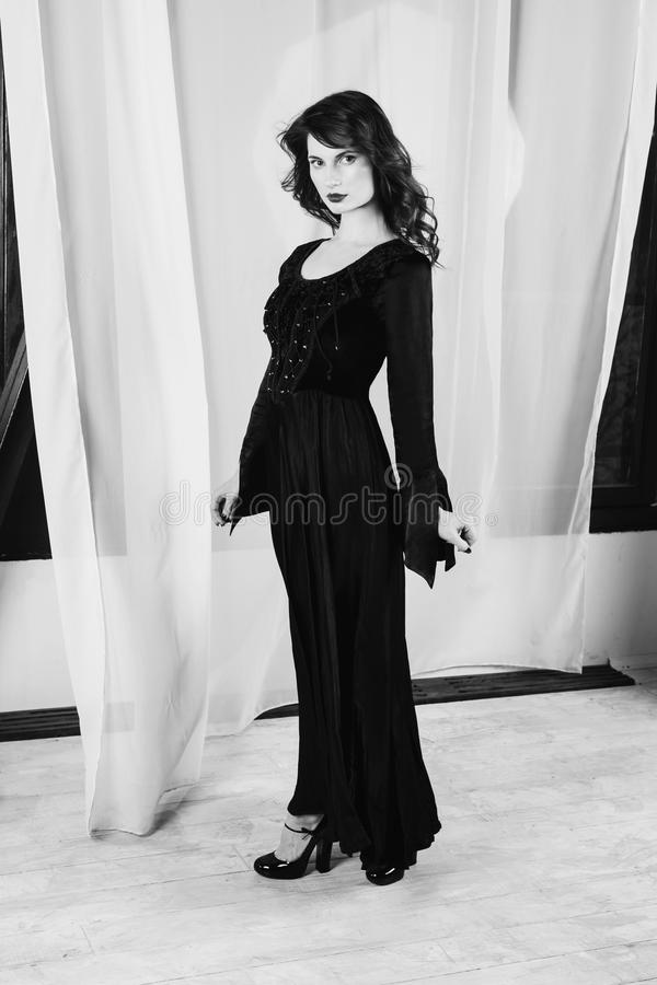 Black and white art monochrome photography. Beautiful girl with long hair and natural make-up and pale skin. A woman in a black retro dress stock photography