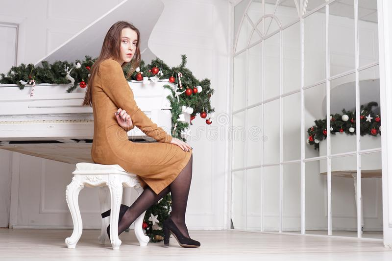 Beautiful girl with long hair near a white piano with Christmas decoration. Beautiful sensual brunette girl with long straight hair near a white piano with royalty free stock photo