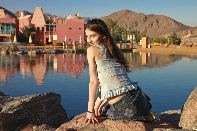 Download Beautiful Girl With Long Hair Is Sitting On Stone Stock Photo - Image: 18018310
