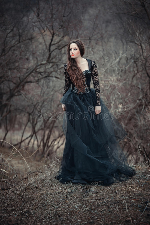 Beautiful girl with long hair. Standing in a black dress standing on the gothic background blowers forests, forest princess, halloween , dark boho , fashionable royalty free stock images