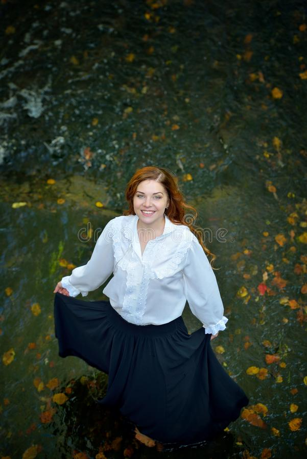 Beautiful girl with long hair in white shirt and black skirt dancing in the river with autumn leaves, looking up and smiling. stock photography