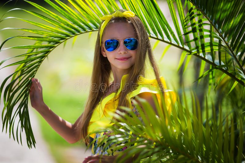 Beautiful girl with long hair in a yellow swimsuit and multi-colored sunglasses on the background of palm trees. Beautiful girl with long hair in yellow swimsuit stock photo