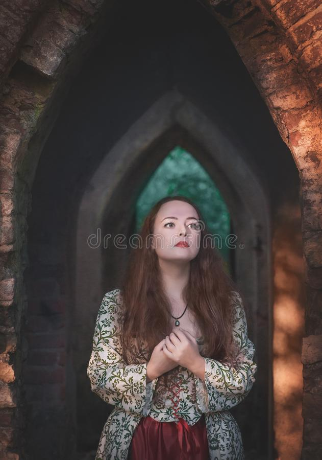 Beautiful girl in long medieval dress in ruins royalty free stock photos