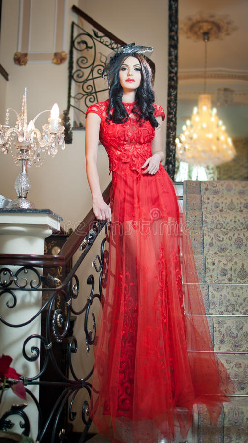 The beautiful girl in a long red dress posing in a vintage scene. royalty free stock image