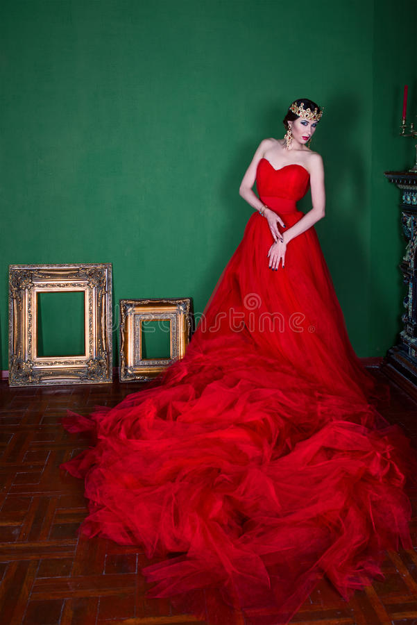 Beautiful girl in long red dress and in royal crown royalty free stock photo