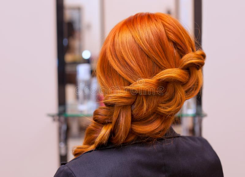 Beautiful girl with long red hair, braided with a French braid, in a beauty salon stock photos