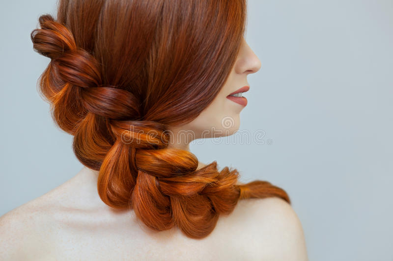 Beautiful girl with long red hair, braided with a French braid, in a beauty salon. stock photos