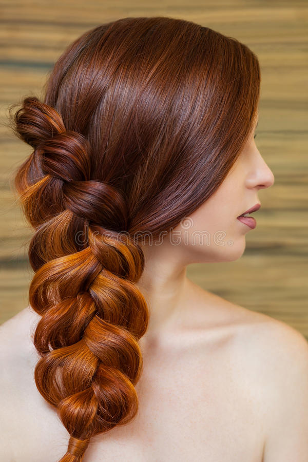 Beautiful girl with long red hair, braided with a French braid, in a beauty salon stock photography