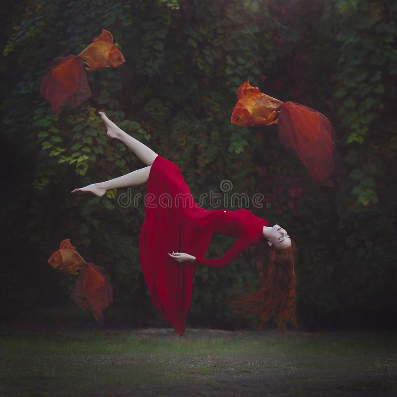 A beautiful girl with long red hair in a red dress is levitating above the ground. Surreal magic photo of a woman with stock images