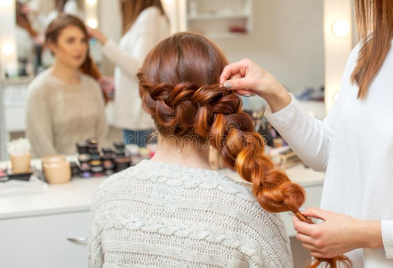 Beautiful girl, with long, red-haired hairy. hairdresser weaves a French braid, close-up. In a beauty salon. Professional hair care and creating hairstyles stock images
