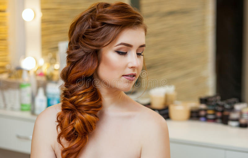 Beautiful girl, with long, red-haired hairy. Hairdresser weaves a French braid, close-up in a beauty salon stock image