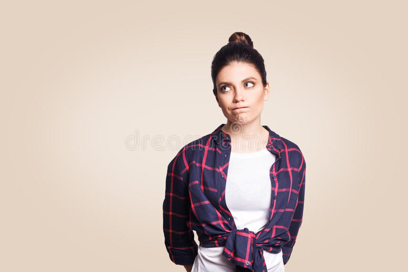 Beautiful girl looking away, having doubtful and indecisive face expression, pursuing her lips as if forbidden to say anything. royalty free stock photos