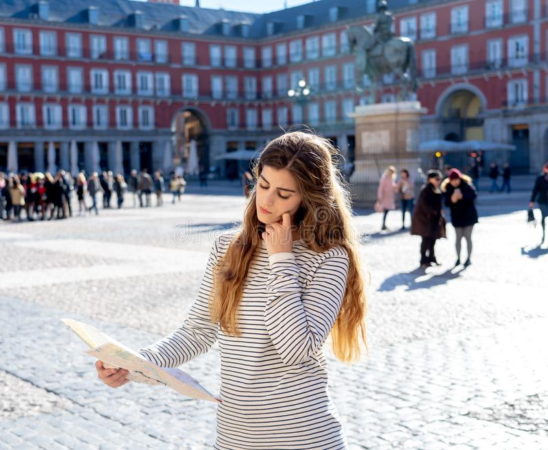 Beautiful girl looking at a map in Plaza Mayor Madrid feeling lost and looking for directions stock photography
