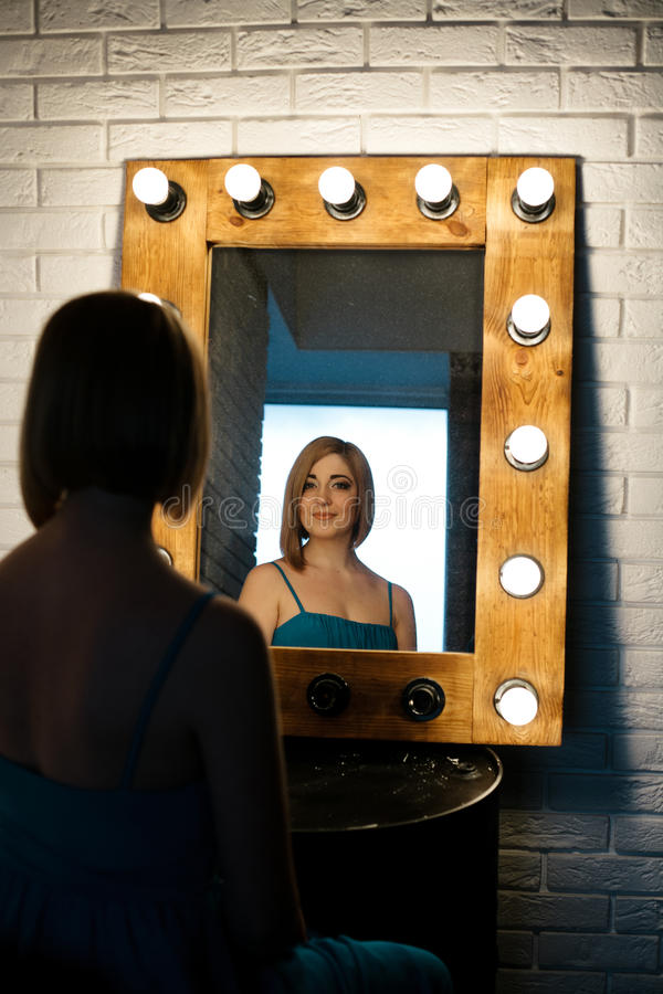 Beautiful girl looking through the mirror in dressing room. Beautiful girl looking through the mirror with many lightbulbs in dressing room stock images