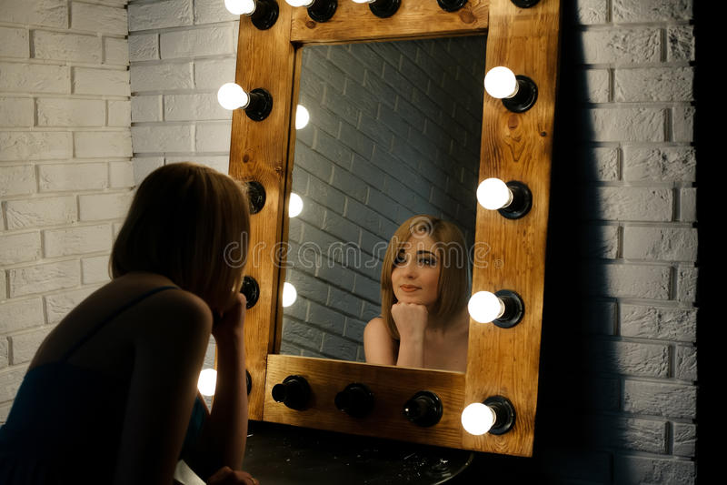Beautiful girl looking through the mirror in dressing room. Beautiful girl looking through the mirror with many lightbulbs in dressing room stock image