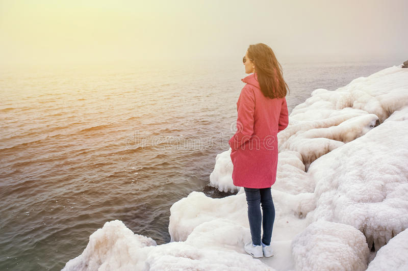 Beautiful girl looks into the distance the sea on the rocks stock photos