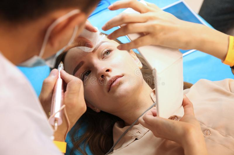 Beautiful girl looks at her eyebrows at the end of the procedure of tattooing eyebrows royalty free stock photography