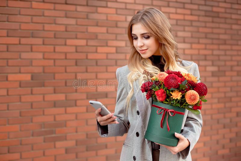 Beautiful girl looks into the phone in her hands holding a green box with bright colors. stock photo