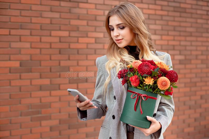 Beautiful girl looks into the phone in her hands holding a green box with bright colors. Beautiful girl looks into the phone in her hands holding a green box stock photography