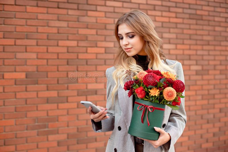 Beautiful girl looks into the phone in her hands holding a green box with bright colors. Beautiful girl looks into the phone in her hands holding a green box royalty free stock photography
