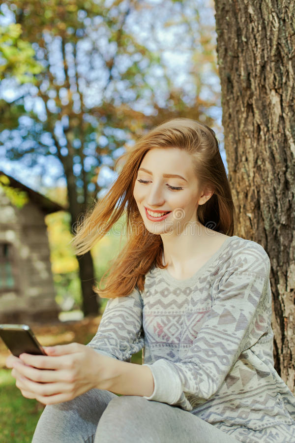Beautiful girl looks on the phone. Beautiful girl with long blond hair and blue eyes looks on the phone. Location of autumn park stock photography