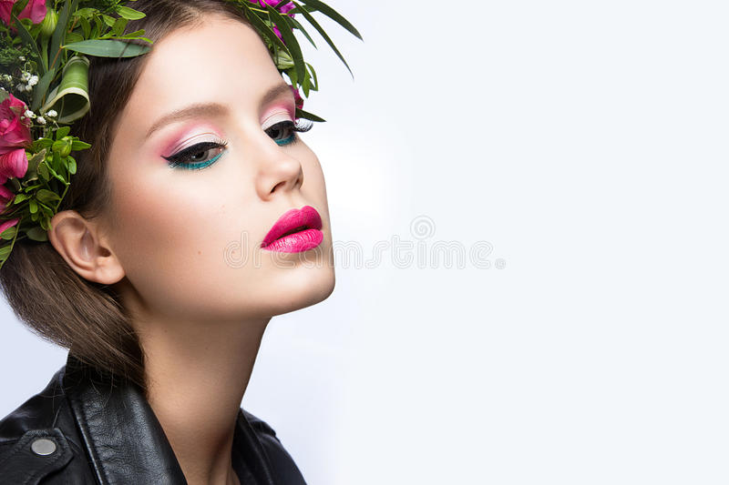 Beautiful girl with a lot of flowers in their hair and bright pink make-up. Spring image. Beauty face. Picture taken in the studio on a white background royalty free stock photos
