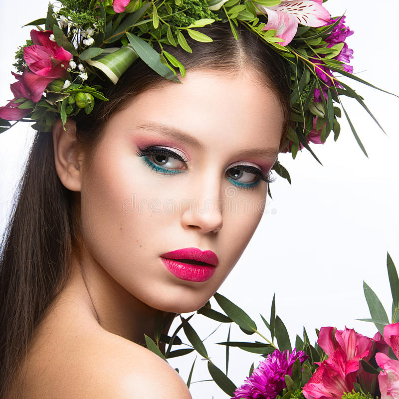 Beautiful girl with a lot of flowers in their hair and bright pink make-up. Spring image. Beauty face. Picture taken in the studio on a white background stock photography