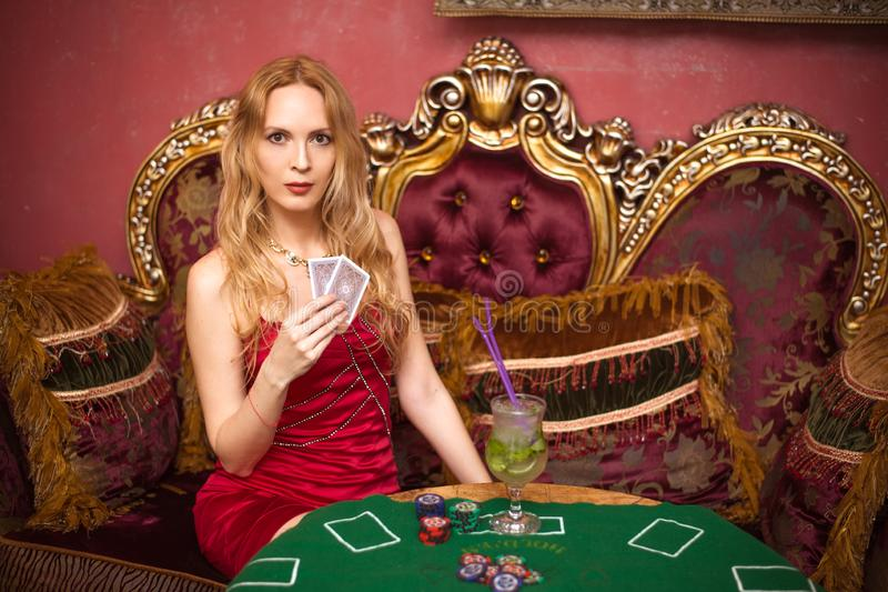 A beautiful girl sits on a couch playing poker on green cloth and holds playing cards in her hands. A beautiful girl among luxurious interiors sits on a couch stock image