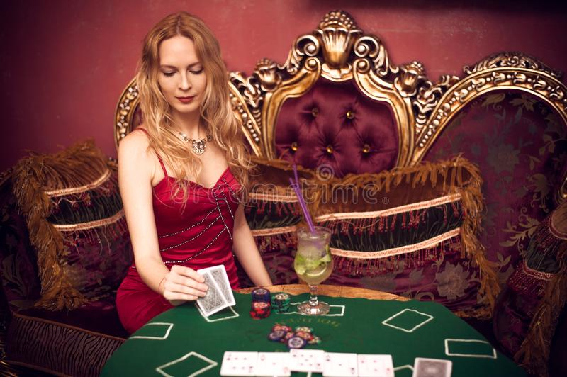 A beautiful girl sits on a couch playing poker on green cloth and holds playing cards in her hands royalty free stock photo