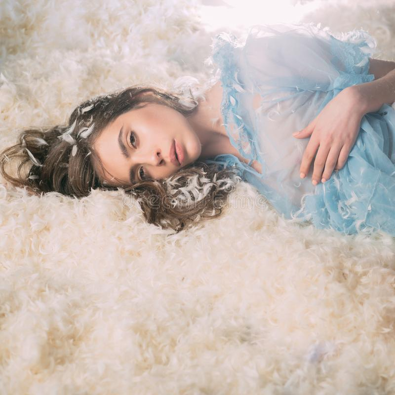 Beautiful girl lying on bed in middle of feathers and looking at camera. Woman in tender pajama relaxing. Airiness. Concept. Lady in transparent blue nightie stock images