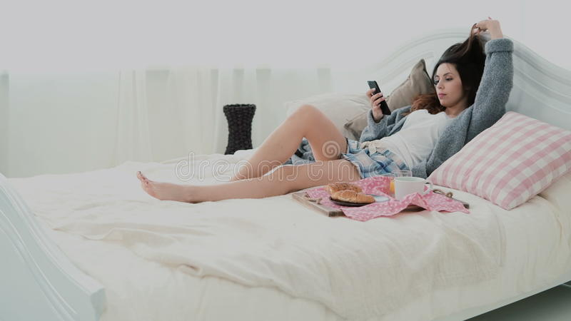 Beautiful girl lying on the bed in morning and using smartphone. Young woman typing, browsing the Internet and yawning. stock image