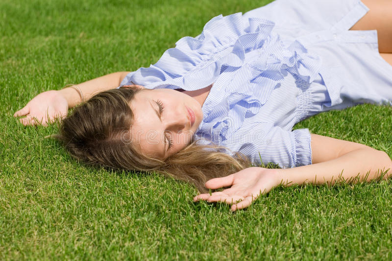 Beautiful girl lying down of grass stock images
