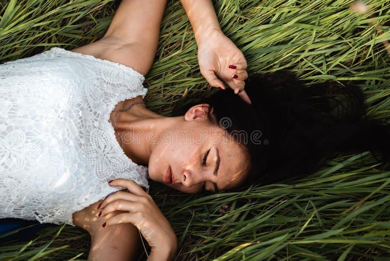 Beautiful girl lying down at grass royalty free stock image